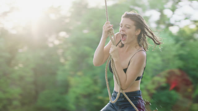 vidéos et rushes de ws slo mo. girl screams as she jumps from rope swing into river. - corde