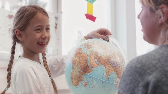 girl searching for a location on the globe in the classroom - mappamondo video stock e b–roll