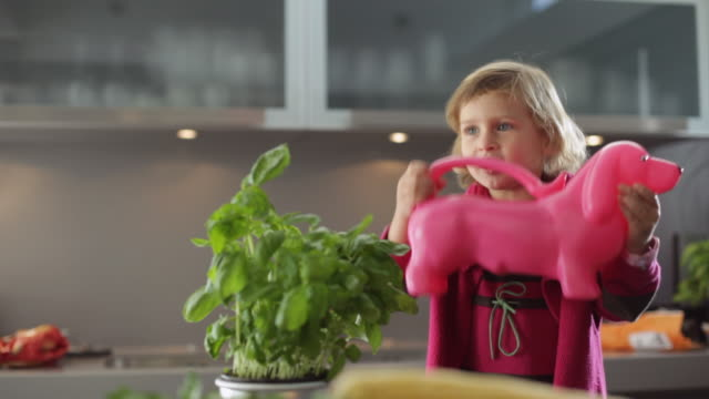 ms girl (2-3) shaking dog-shaped watering can in kitchen / kleinmachnow, brandenburg, germany - watering can stock videos & royalty-free footage