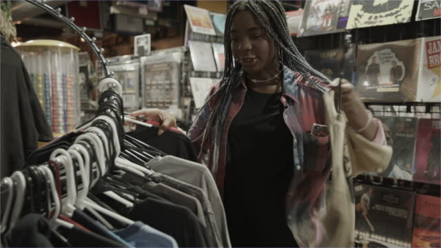 stockvideo's en b-roll-footage met girl shopping for t-shirts in music store / provo, utah, united states - shaky