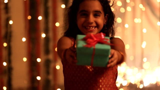 MS Girl showing gift box and smiling in diwali festival