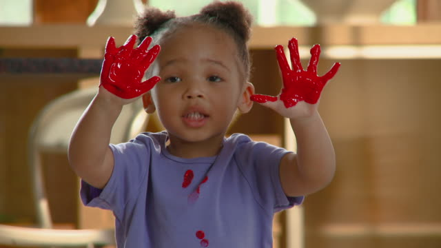 cu girl showing her messy hands covered in red paint / richmond, virginia, usa - malen stock-videos und b-roll-filmmaterial