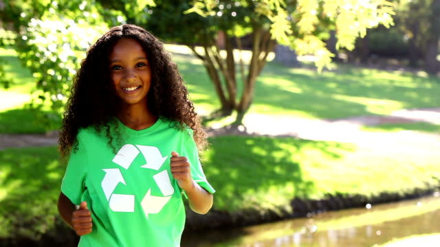 Girl showing her recycling tshirt in the park