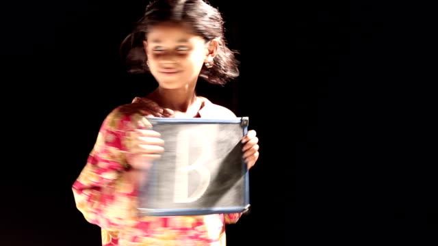 stockvideo's en b-roll-footage met girl showing slate - letter b