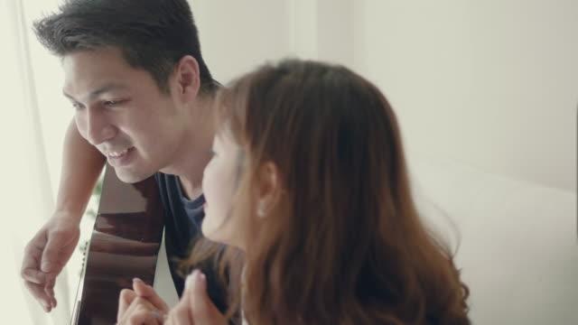 Fille qui chante alors que son petit ami jouer de la guitare sur le canapé.