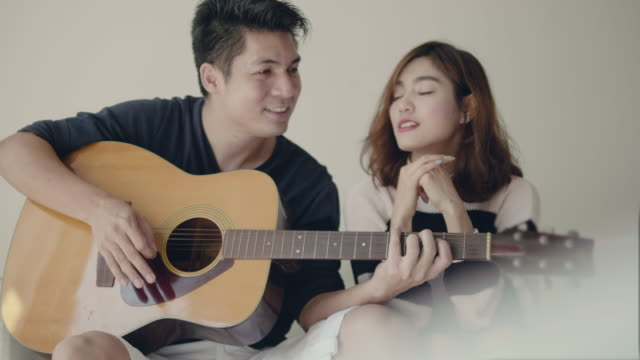girl singing while her boyfriend playing guitar on sofa. - plucking an instrument stock videos and b-roll footage