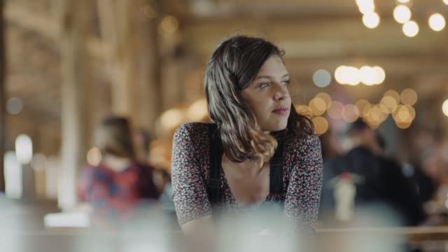 vídeos de stock e filmes b-roll de ms slo mo. girl sits alone and looks around in restaurant dining area. - olhar em redor
