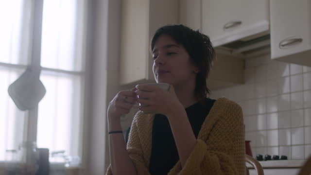 girl sits alone in kitchen sipping hot beverage - cardigan sweater stock videos & royalty-free footage
