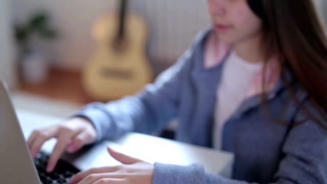 girl sits at the table and use a laptop - petite teen girl stock videos and b-roll footage