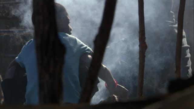 vídeos de stock e filmes b-roll de girl sits by smoking fire, cape maclear, malawi - malávi