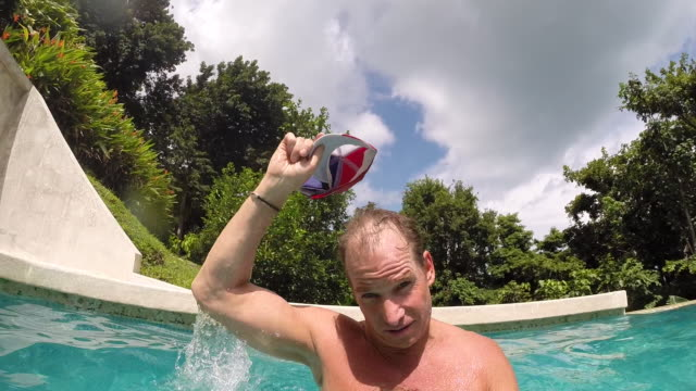 vídeos de stock e filmes b-roll de girl sits on air mattress in pool and father picks up girl and spins her around on his head then throws her into pool on mattress - kelly mason videos