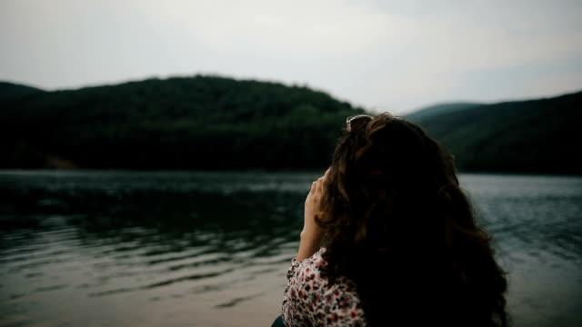 vídeos y material grabado en eventos de stock de chica sentada en un lago disfrutando de la impresionante vista - espalda humana