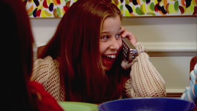vidéos et rushes de cu, pan, girl (10-11) sitting at table and talking on phone while friend (10-11) eating popcorn - téléphone sans fil