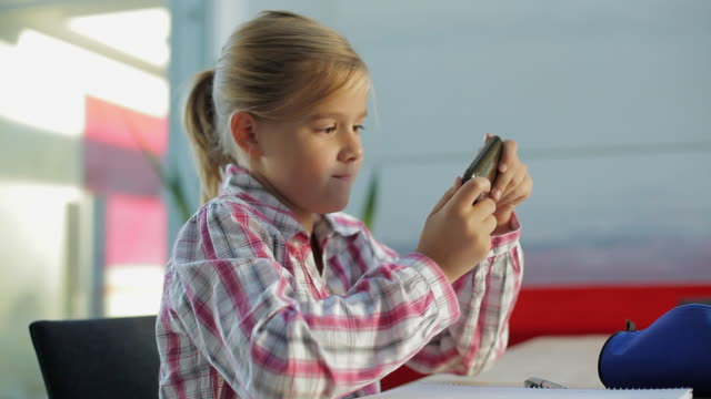 MS Girl (10-11) sitting at table playing game on mobile phone / Kleinmachnow, Brandenburg, Germany