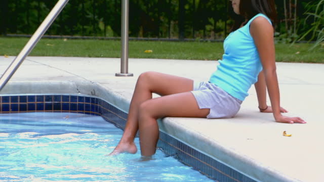 girl sitting by a pool feet splashing in water - one teenage girl only stock videos & royalty-free footage