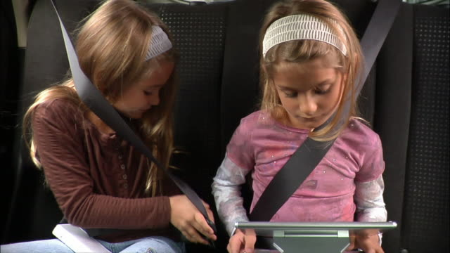 Girl sitting down next to twin sister in back seat of car and securing seat belt around self / sisters playing video games on portable devices