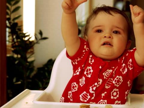 girl sitting in a high chair lifting her arms and moving her fingers sweden. - människofinger bildbanksvideor och videomaterial från bakom kulisserna
