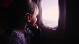 Girl sitting in an airplane, looking out the window at the rising sun
