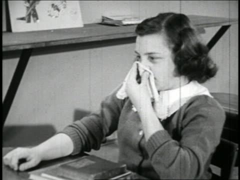 b/w 1940 girl sitting in classroom sneezing in handkerchief / educational - sneezing stock videos & royalty-free footage