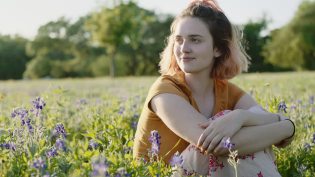 MS SLO MO. Girl sitting in field of flowers gazes off and daydreams.