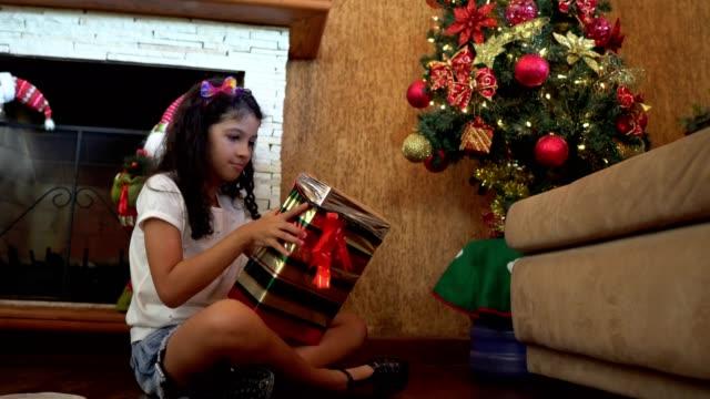 vídeos de stock e filmes b-roll de girl sitting in front of christmas tree opening gift - américa latina
