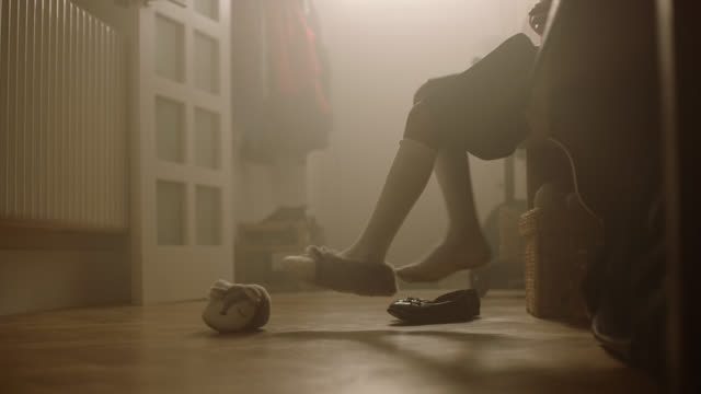 girl sitting in hallway putting on shoes - anticipation stock-videos und b-roll-filmmaterial