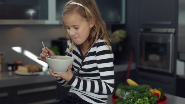 ms girl (10-11) sitting in kitchen eating bowl of cornflakes / kleinmachnow, brandenburg, germany - bowl stock videos and b-roll footage