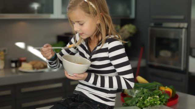 vídeos y material grabado en eventos de stock de ms tu girl (10-11) sitting in kitchen eating bowl of cornflakes / kleinmachnow, brandenburg, germany - cereal