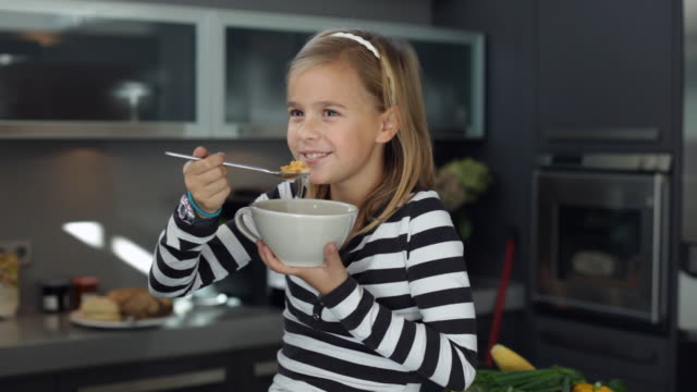 MS Girl (10-11) sitting in kitchen eating bowl of cornflakes / Kleinmachnow, Brandenburg, Germany