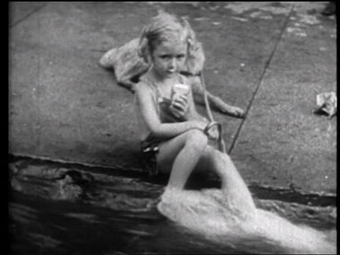 vidéos et rushes de b/w 1939 girl sitting in running water in gutter licking ice cream / nyc / travelogue - une seule petite fille