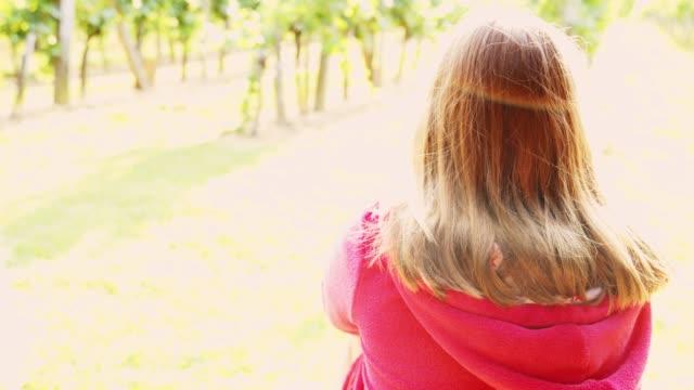 stockvideo's en b-roll-footage met meisje zit in zonnige ochtend wijngaard, real-time - alleen tienermeisjes