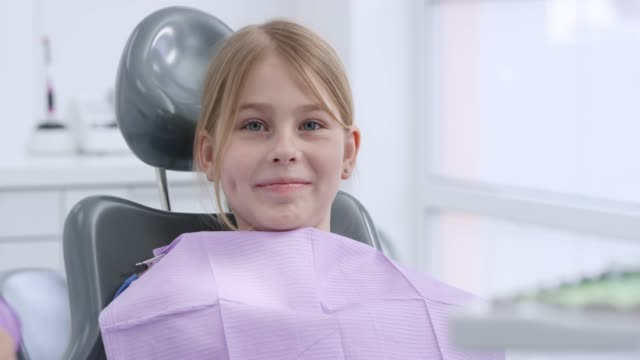 vídeos de stock e filmes b-roll de girl sitting in the dental chair and smiling - dentista