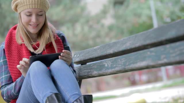 girl sitting on a bench and chatting on tablet pc - neckwear stock videos and b-roll footage
