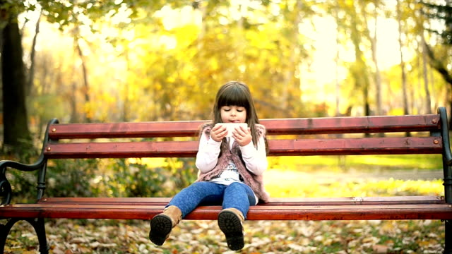 Girl sitting on a bench and using phone