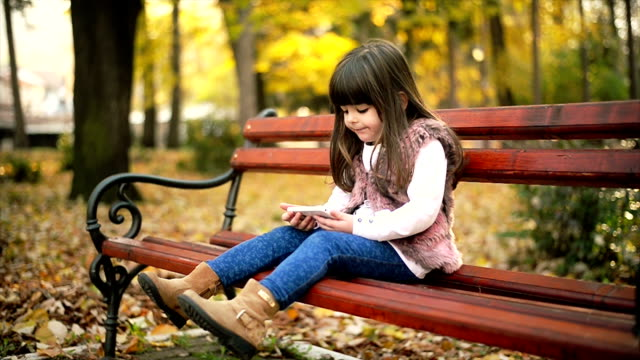 girl sitting on a bench and using phone - hair toss stock videos & royalty-free footage