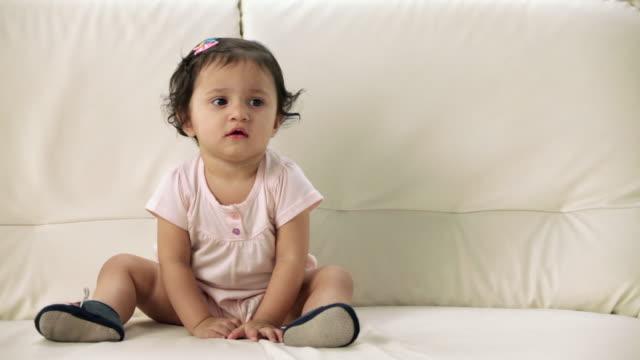 vídeos de stock, filmes e b-roll de girl sitting on a couch  - vida de bebê