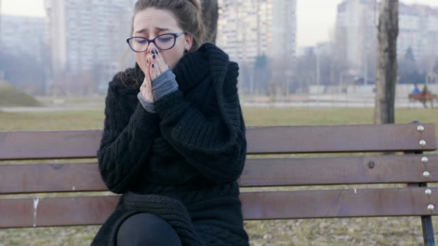 girl sitting on a park bench in the cold weather and trying to warm herself - bench stock videos & royalty-free footage
