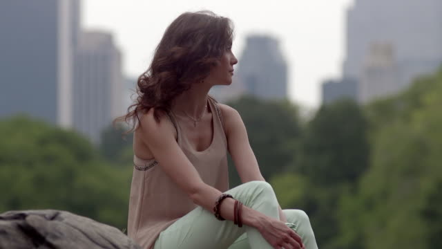 A girl sitting on a rock in Central Park looks sad and looks away.