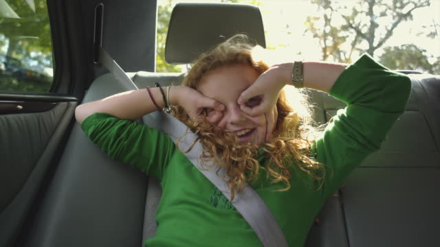 ms girl (10-11) sitting on back seat of car, playing / atlanta, georgia, usa - pulling funny faces stock videos & royalty-free footage