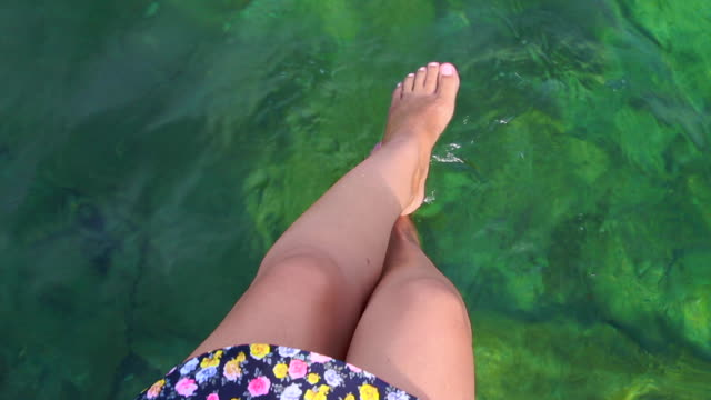Girl sitting on beach dock with feet on water contemplating the Mediterranean Sea Costa Brava from elevated viewpoint with the green waters.