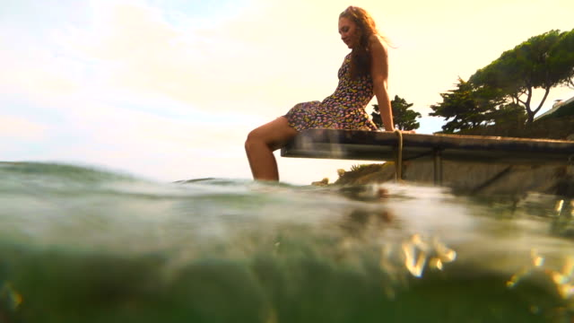 vidéos et rushes de girl sitting on beach dock with feet on water contemplating the mediterranean sea costa brava with sunset light and with underwater view. - robe d'été