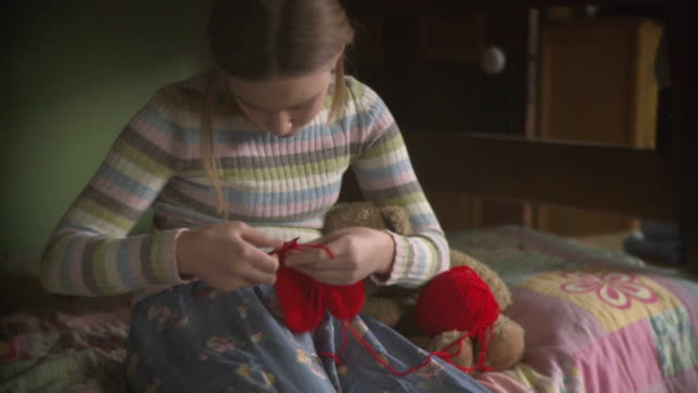 MS PAN Girl (10-11) sitting on bed crocheting heart / Newark, Illinois, USA