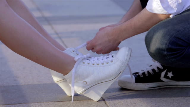 vídeos de stock, filmes e b-roll de girl sitting on bench tying her white shoes at park then a men ties it for her - amarrar