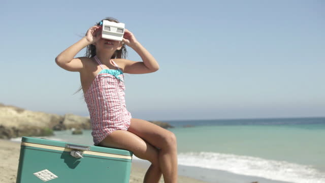 girl sitting on coolbox looking through slide viewer on beach - cool box stock videos and b-roll footage