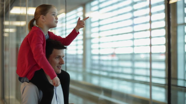 MS Girl (6-7) sitting on daddy's shoulders looking out of airport window / Toulouse, Haute-Garonne, France