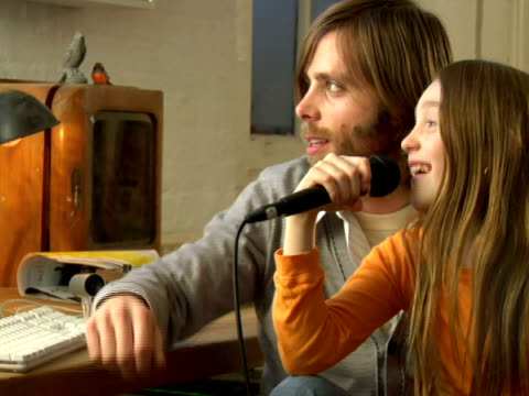 cu,   girl (10-11)  sitting on father's laps,   singing - 10 11 anni video stock e b–roll