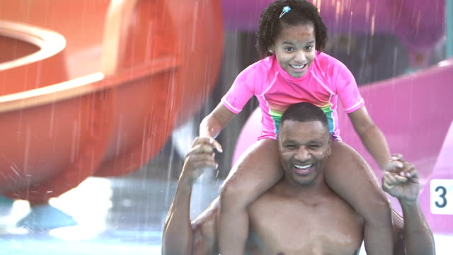 Girl sitting on father's shoulders at water park