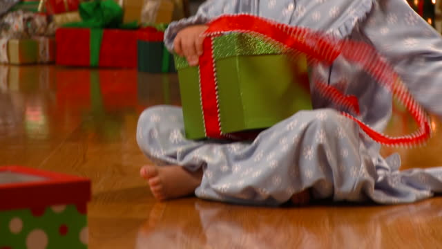 CU, TU, Girl (4-5) sitting on floor and opening present, Christmas tree in background, Richmond, Virginia, USA