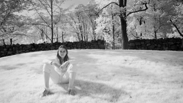 ws girl sitting on grass by stone wall / farmington, connecticut, usa - connecticut stock-videos und b-roll-filmmaterial
