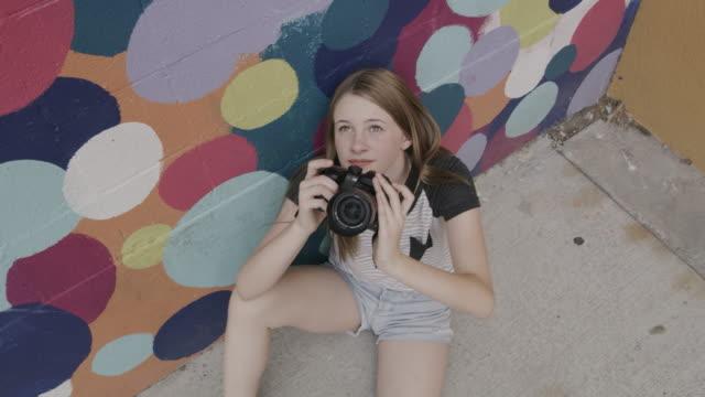 girl sitting on ground near dotted wall photographing with camera / provo, arizona, united states - カメラマン点の映像素材/bロール
